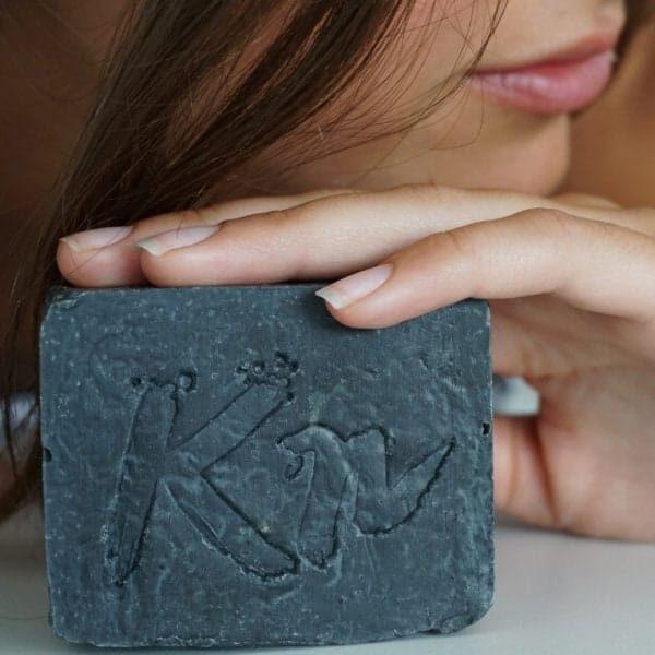 Kundin hält Seife mit Aktivkohle